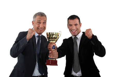 awards ceremony: cheerful businessmen holding a golden cup Stock Photo