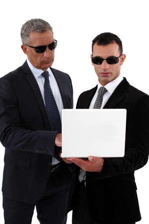 subversive: Businessmen wearing sunglasses and looking at a laptop