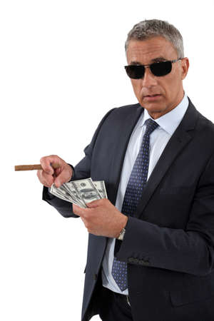 american banker: Businessman with a cigar and a fistful of dollars Stock Photo