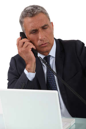 Mature businessman taking important call photo