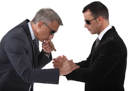 cosa: Mobster helping his boss light a cigar