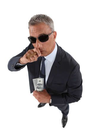 A crook holding stolen money and smoking a cigar photo