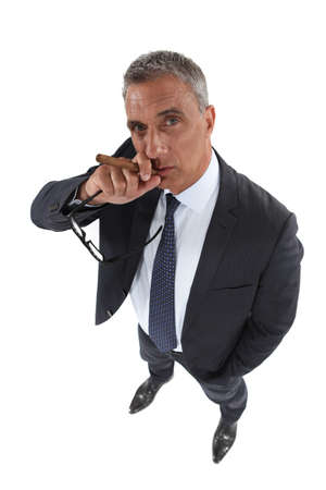 cigare: A mature businessman smoking a cigare.