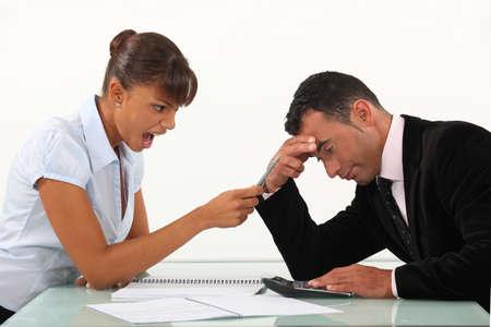 jefe enojado: Mujer que grita a un hombre al otro lado de un escritorio