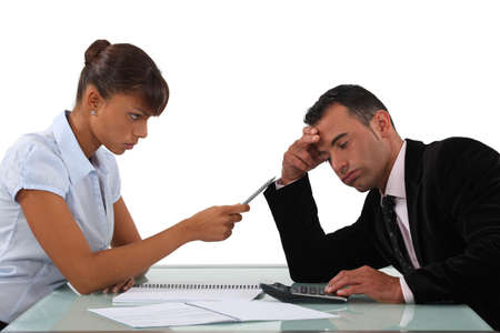 monthly salary: Stern woman with a man using a calculator