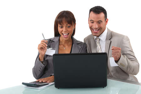 office environment: Cheerful business professionals watching a video on their laptop