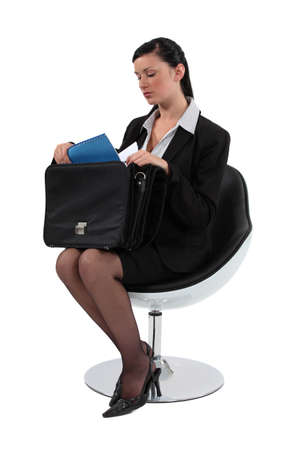 furnish: Woman sat removing document from briefcase Stock Photo