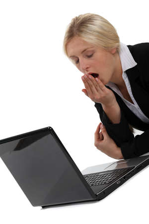 mouth closed: Woman yawning in front of computer