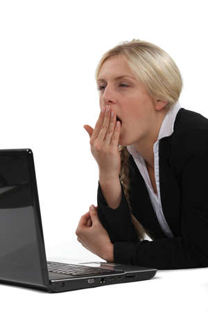 drowsiness: Woman yawning in front of computer