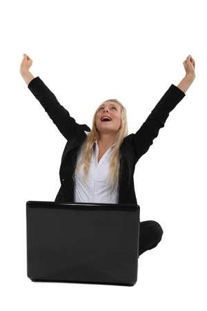 triumphant: Triumphant businesswoman sitting at a laptop Stock Photo
