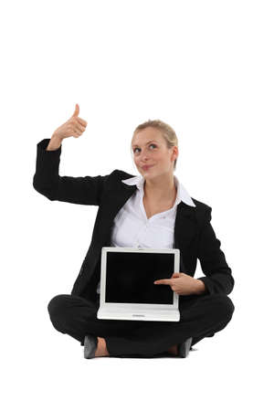 Thumbs up from a businesswoman for the blank screen on her laptop photo