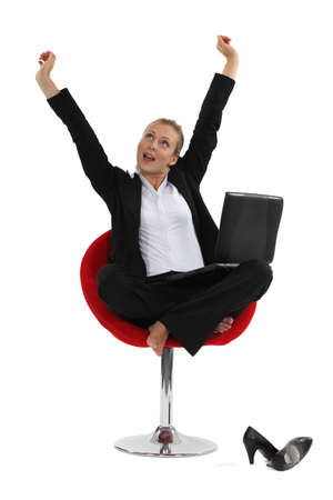 Woman sitting cross-legged in a chair and stretching her arms
