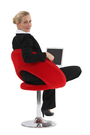 Businesswoman sitting in a funky chair with a laptop photo