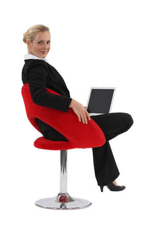 designer chair: Businesswoman sat in designer chair with laptop Stock Photo