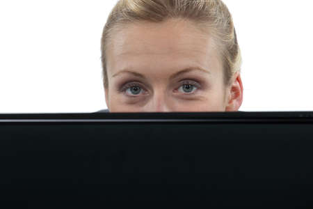 obscured face: Woman hiding behind laptop computer Stock Photo