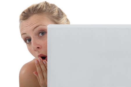 Surprised woman peering out from behind her laptop photo