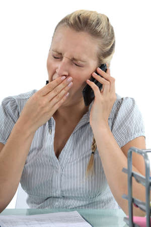 woman talking on the phone and yawning photo