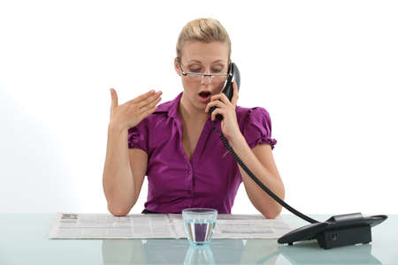 defamation: Surprised woman reading a newspaper whilst on the phone