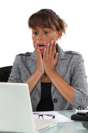 Shocked woman looking at computer screen photo