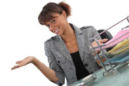 Happy receptionist presenting her work area photo