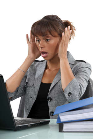 alarmed: Alarmed woman looking at her laptop
