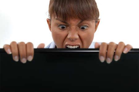 freaks: Businesswoman biting laptop screen