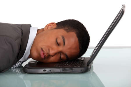 catnap: Young businessman asleep on laptop
