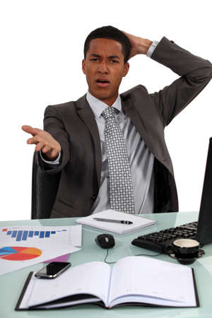 back problem: Troubled businessman remonstrating with the audience Stock Photo