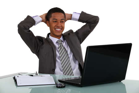 settle back: Relaxed businessmen smiling at his laptop