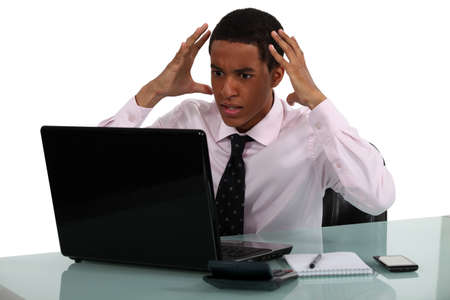 angst: Frustrated young businessman being driven crazy by his computer