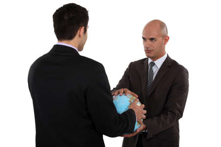 Two businessmen holding globe Stock Photo - 20018379