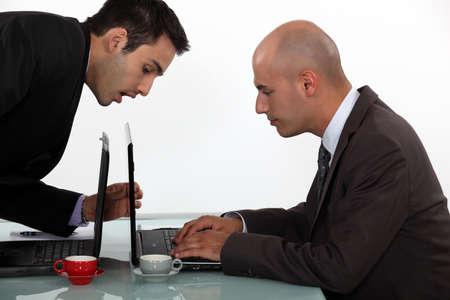 sneaking: Businessman sneaking a peak at his colleagues work