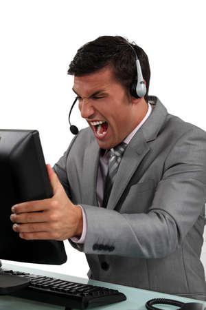 irked: Businessman shouting at his computer Stock Photo