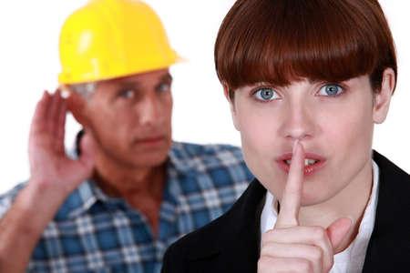 Female office worker making shush gesture Stock Photo