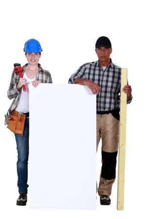 Plumber and carpenter stood by blank poster photo