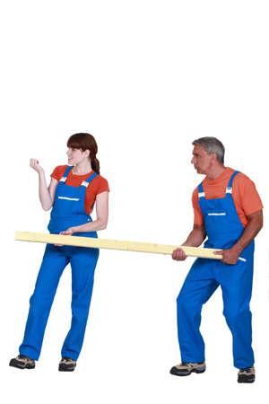 obrero: Trabajador que controla sus uñas mientras que su colega toma el peso de una carga pesada Foto de archivo