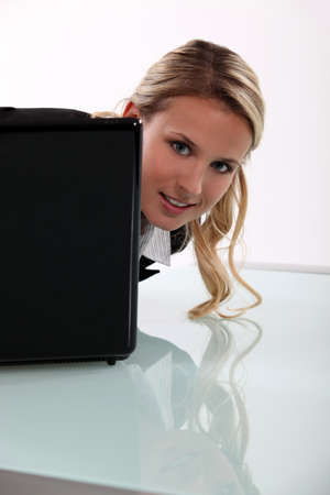 Young woman peering around her laptop photo