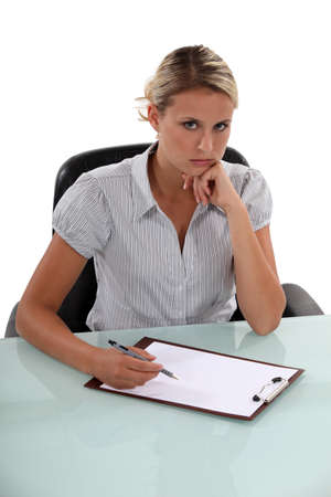 grudging: Standoffish woman writing on a clipboard