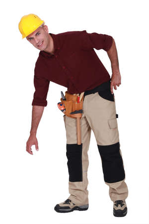 knees bent: Tradesman bending over to pick something up Stock Photo