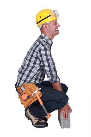 contorted: Tradesman struggling to lift a block