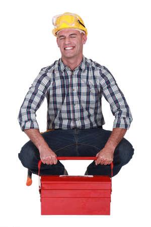 feeble: Tradesman struggling to lift his toolbox