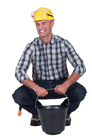 en cuclillas: Trabajador que lucha por levantar un pesado cubo