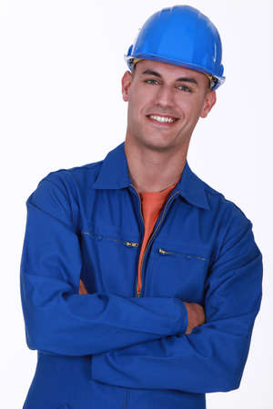 blue overall: smiling construction worker with folded arms
