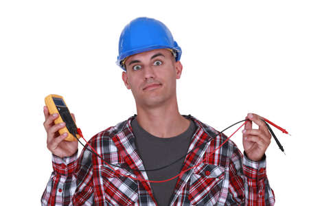 incertitude: A wide-eyed tradesman holding a multimeter