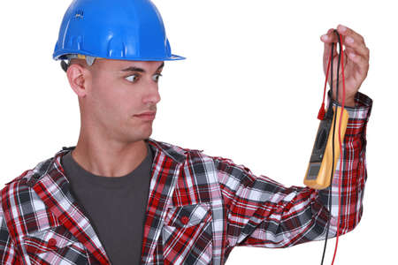 incredible: Wide-eyed tradesman staring at a multimeter Stock Photo