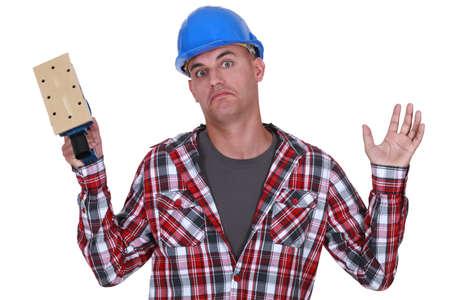 sander: Construction worker holding up a sander