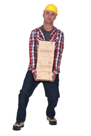 Tradesman carrying a heavy load of bricks photo