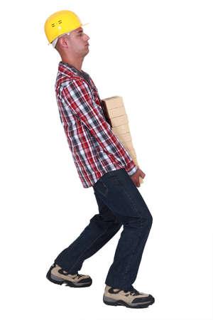 carries: Mason carrying pile of bricks