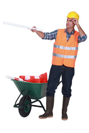 Road worker with a barrow full of cones Stock Photo