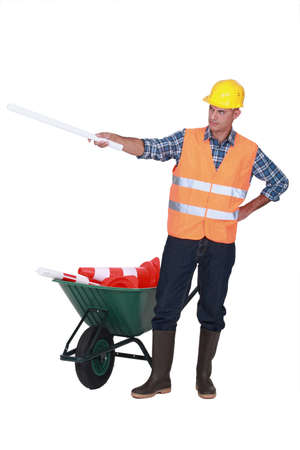 road worker: Foreman with plans and a barrow of traffic cones